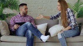 Il litigio turbato delle coppie dei giovani a causa dell'uomo ha la dipendenza da Internet e suo grido del girlfrieng lui che pro immagine stock