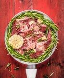 Il lombo crudo dell'agnello taglia con i rosmarini e l'aglio in padella bianca su fondo di legno rosso, vista superiore Immagini Stock Libere da Diritti