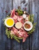 Il lombo crudo dell'agnello taglia la carne a pezzi con petrolio, pepe e condimento sul fondo di legno blu Fotografie Stock Libere da Diritti