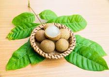 Il longan fresco con la foglia del longan ha messo sulla tavola di legno Immagine Stock Libera da Diritti