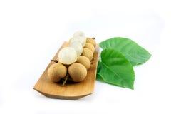 Il Longan fresco sul piatto di bambù, ha foglie disposte accanto. Immagini Stock