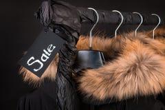 il lotto dei cappotti neri, rivestimento con pelliccia sui vestiti d'attaccatura del cappuccio tormenta Fondo Iscrizione di vendi Immagini Stock