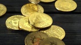 Il lotto delle monete del bitcoin cade sulla superficie di legno Fine in su video d archivio