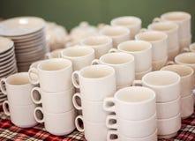 Il lotto delle tazze di tè ha impilato uno su una, approvvigionando su un banchetto Immagini Stock Libere da Diritti