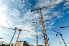 Il lotto di alte gru a torre lavora alla costruzione di nuovo buildin Fotografia Stock Libera da Diritti