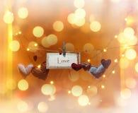 Il lotto di cuore multicolore e l'iscrizione amano su fondo brillante Fotografia Stock