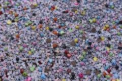 Il lotto di piccola plastica variopinta ha colorato i cubi con le lettere, religiose ed altri segni popolari come il OM firmano Immagine Stock
