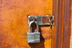 Il lucchetto d'argento sulla vecchia porta arrugginita ha lasciato sbloccato dove chiunque può ottenere i colori vibranti in- di  Fotografia Stock Libera da Diritti