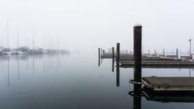 Il lungomare ed il canottaggio si mettono in bacino su una mattina nebbiosa Immagine Stock Libera da Diritti