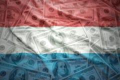 Il Lussemburgo d'ondeggiamento variopinto diminuisce su un fondo dei soldi del dollaro Fotografia Stock