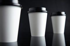 Il lusso bianco porta via nero messo delle tazze di carta rispecchiato Fotografie Stock Libere da Diritti