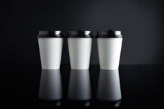 Il lusso bianco porta via nero messo delle tazze di carta rispecchiato Fotografie Stock