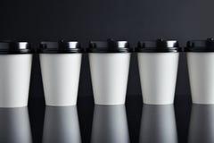 Il lusso bianco porta via nero messo delle tazze di carta rispecchiato Immagine Stock