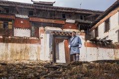 Il mаn del Bhutan in Bhutanese tradizionale copre sui precedenti delle costruzioni dei monas di Padjoding fotografia stock