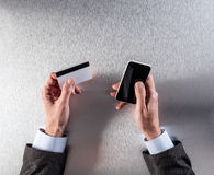 il M.-commercio con l'uomo d'affari passa la carta di credito ed il telefono della tenuta Immagini Stock Libere da Diritti