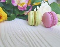 Il macaron colorato è aumentato su un fondo di legno bianco, alstroemeria Immagine Stock