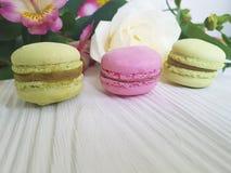 Il macaron colorato Francia è aumentato su un fondo di legno bianco, alstroemeria Fotografia Stock Libera da Diritti