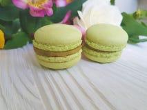 Il macaron dolce colorato Francia è aumentato su un fondo di legno bianco, alstroemeria Fotografie Stock Libere da Diritti