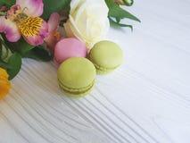Il macaron dolce colorato Francia tradizionale è aumentato su un fondo di legno bianco, alstroemeria Fotografia Stock