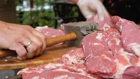 Il macellaio batte i pezzi di carne di maiale con un grande martello Il cuoco prepara la carne prima della cottura Una montagna g stock footage