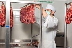 Il macellaio controlla la salsiccia Immagini Stock