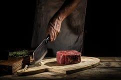 Il macellaio del cuoco unico prepara la bistecca di manzo fotografia stock libera da diritti