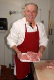 Il macellaio mostra le braciole di maiale Immagini Stock Libere da Diritti