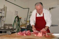 Il macellaio prepara gli arrosti senz'ossa del mandrino Fotografia Stock