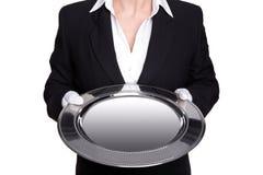 Il maggiordomo femminile che tiene un cassetto d'argento ha isolato. Fotografia Stock
