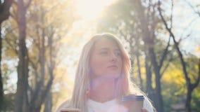 Il maglione bianco d'uso della bella giovane ragazza dei pantaloni a vita bassa facendo uso dello Smart Phone ed il caffè bevente archivi video