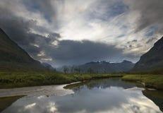 Il maltempo che si avvicina in valle della montagna sopra il paesaggio del fiume fotografia stock libera da diritti