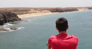 Il Man è sedentesi e guardante alle onde dell'Oceano Atlantico sulla spiaggia di Papagayo a Lanzarote, isole Canarie archivi video