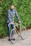 Il mand dei pantaloni a vita bassa con la barba ed il suo fixie bike Fotografia Stock Libera da Diritti