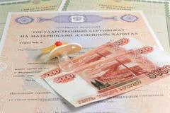 Il manichino del bambino con soldi e materno, certificati di nascita Fotografia Stock