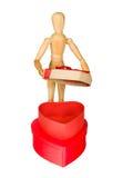 Il manichino di legno apre il contenitore di regalo a forma di cuore Immagine Stock Libera da Diritti
