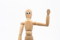 Il manichino di legno con gli occhi googly dice ciao - il fondo bianco fotografia stock libera da diritti