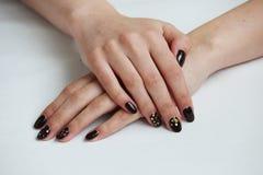 il manicure delicato del caffè di bellezza con oro scintilla con la vernice del gel su un fondo bianco della parete immagine stock libera da diritti