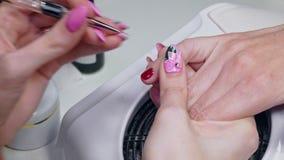 Il manicure dipinge i chiodi con vernice rossa stock footage