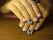 Il manicure eccellentemente ha reso al suo lavoro un bello manicure con un gel polacco sulle sue mani ed il cliente è felice Fotografie Stock