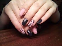 Il manicure eccellentemente ha reso al suo lavoro un bello manicure con un gel polacco sulle sue mani ed il cliente è felice Fotografia Stock