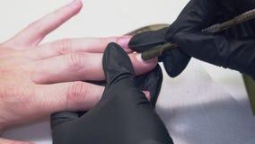 Il manicure in guanti neri ed in una fasciatura prepara le unghie per il primo piano del manicure stock footage