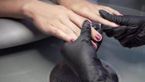 Il manicure prepara i chiodi della ragazza nel salone del chiodo per una procedura di pedicure Primo piano sparato delle mani di  archivi video