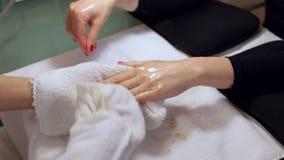 Il manicure pulisce le sue mani con un asciugamano bagnato ad un cliente dopo sfrega e massaggia stock footage