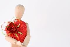 Il Mannequin tiene il regalo di figura del cuore Immagine Stock