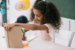 Il manuale afroamericano e la scrittura della tenuta della scolara si esercitano alla lezione Immagini Stock Libere da Diritti