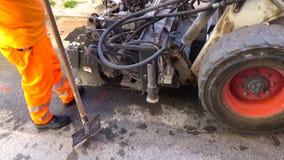 Il manzo di Skid del driver del lavoratore rimuove l'asfalto consumato video d archivio