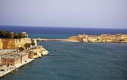Il mar Mediterraneo viene fino ai mura di mattoni ed alle costruzioni che stanno circondando il porto a La Valletta Malta fotografia stock libera da diritti