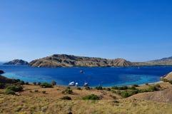 Il mare blu profondo nascosto rimane incastrato in mezzo alla collina ondulata giallastra Immagine Stock
