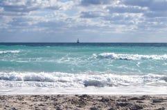 Il mare, con le onde sui precedenti di cielo blu e delle nuvole Immagine Stock