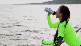 Il mare di sguardo della donna di sport prende un'acqua della bevanda della rottura sull'argine della città archivi video